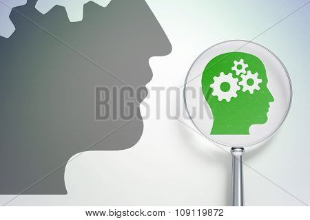 Marketing concept:  Head With Gears with optical glass on digital background
