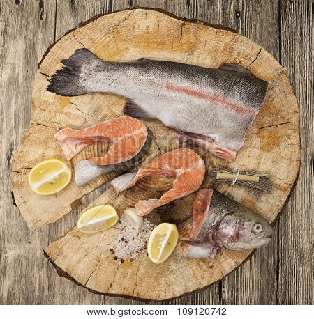 Fresh Norwegian rainbow trout steaks with lemon lies on a wooden background.