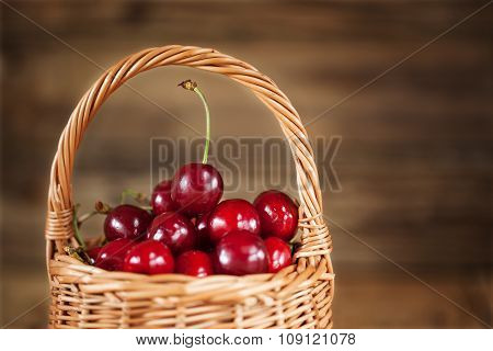Ripe Sweet Cherries in  Basket closeup on Rustic Wooden background