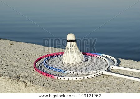Badminton Racquets With Shuttlecock On A Stone Bench Against The Background Of A Sea