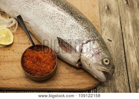 Fresh Norwegian rainbow trout with lemon red caviar, and onions on a wooden background.