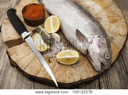 Fresh Norwegian rainbow trout with lemon red caviar, sea salt, knife and onions on a wooden background.