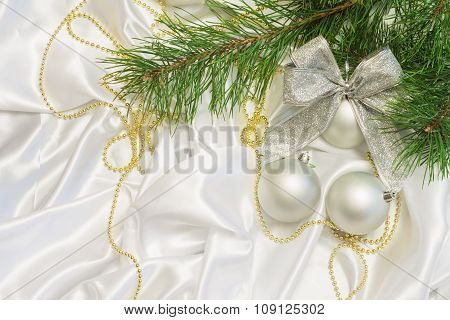 silver Christmas balls with golden beads and pine branch on a wh