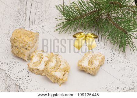 Napoleon cake on lace paper napkin with a sprig of pine