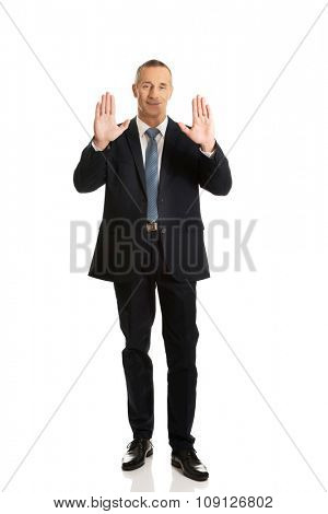 Mature businessman pressing abstract screen.