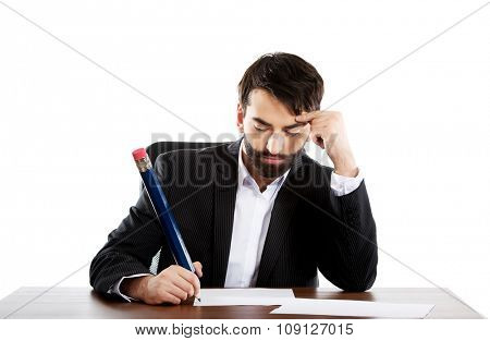 Tired businessman writing with big pencil in the office.