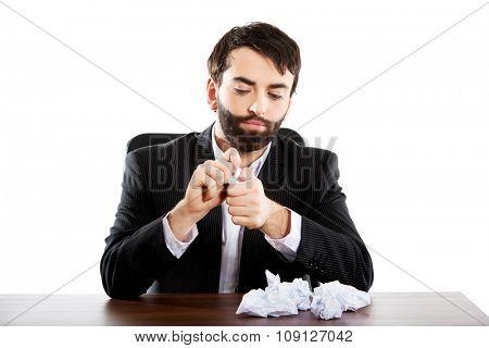 Young worried businessman crushing sheets.