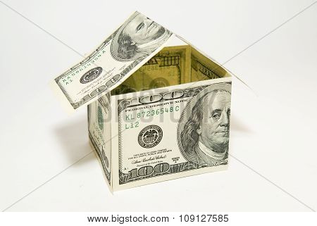 Us Dollar Banknotes On Display In The Shape Of A House On Over White