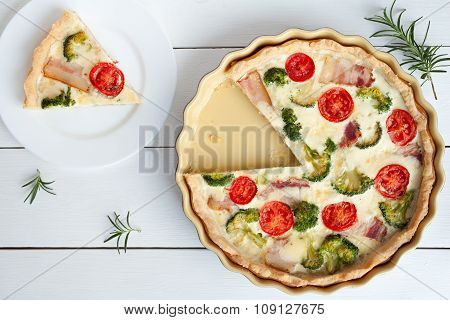 Sliced quiche lorraine traditional homemade french tart pie preparation recipe with tomatoes bacon c