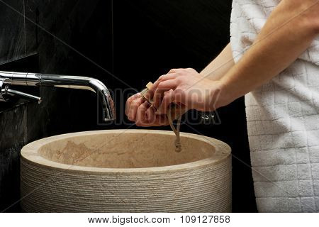 Woman cleaning hands in bathroom.