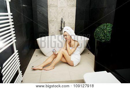 Beautiful woman applying cream on face in bathroom.