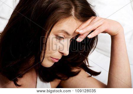 Sad depressed woman sitting on bed.