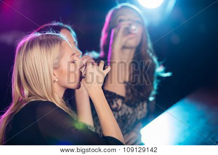 Beautiful girls drinking shots together at the nightclub