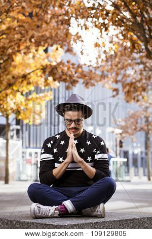 Young man meditating in the city with a hipster style