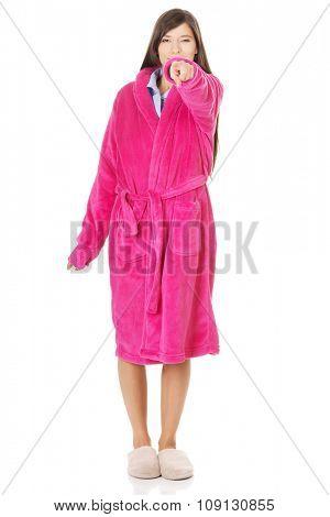 Beautiful woman wearing pink bathrobe pointing on you.