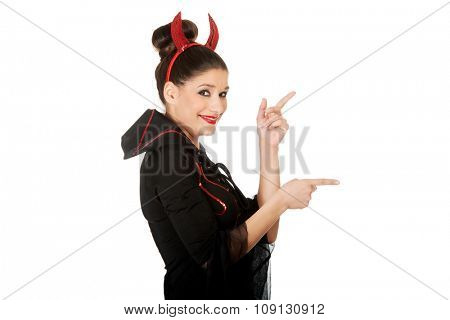 Beautiful woman in devil carnival costume pointing aside.