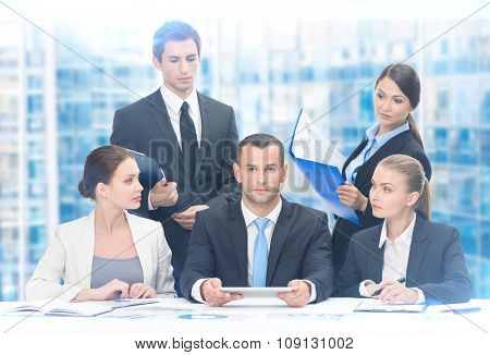 Group of managers discussing strategy while sitting at the table, blue  background. Concept of teamwork and cooperation