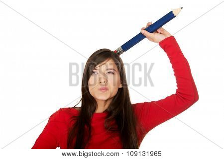 Beautiful young student woman with a big pencil on head.