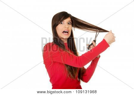 Young shocked woman cutting her hair.