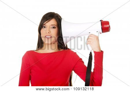 Young woman with megaphone near ear.