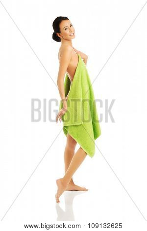 Side view woman standing wrapped in towel.