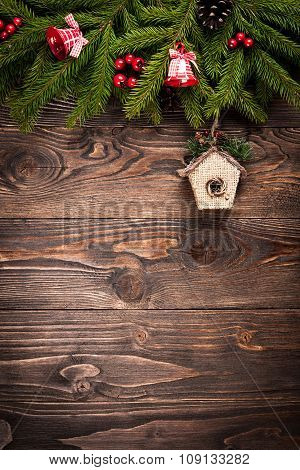 Fir Tree Decorated Bells And Birdhouse On Dark Wooden Background