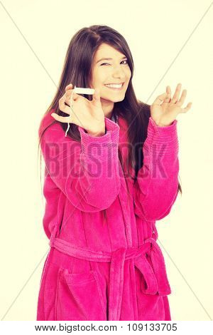 Caucasian woman in pink bathrobe with tampon.