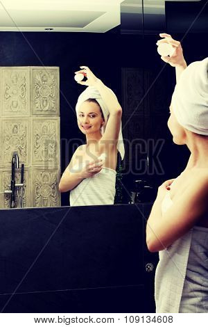 Woman using deodorant in the bathroom.