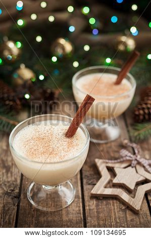 Eggnog christmas season traditional homemade alcohol liqueur drink in two glass cups preparation rec