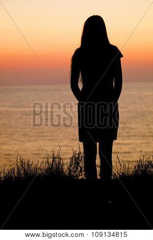 Girl stands on a sea show at sunset