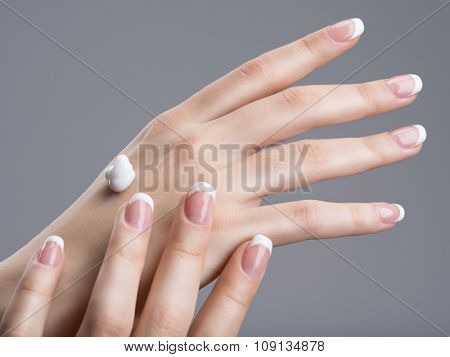 Close-up female hands applly hand cream.  with french manicure on nails