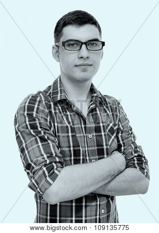 Blue toned black and white portrait of young man wearing glasses and checkered shirt standing with crossed arms