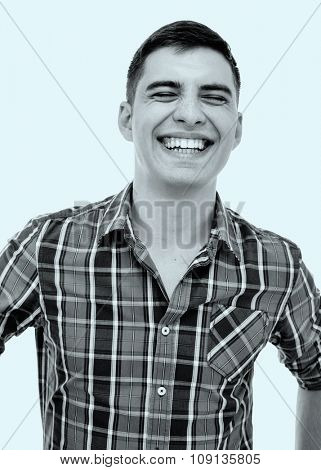 Blue toned black and white portrait of young man wearing checkered shirt laughing out loud with closed eyes - laughter concept