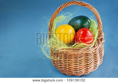 Easter Eggs Painted with red, yellow colors and green in the Basket on the woden table