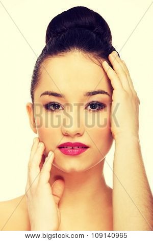 Beautiful woman with full make up touching head.