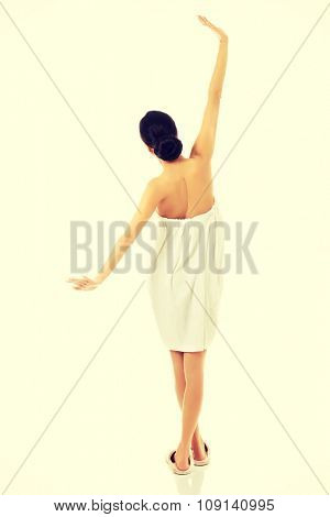 Spa woman wrapped in towel stretching her arms