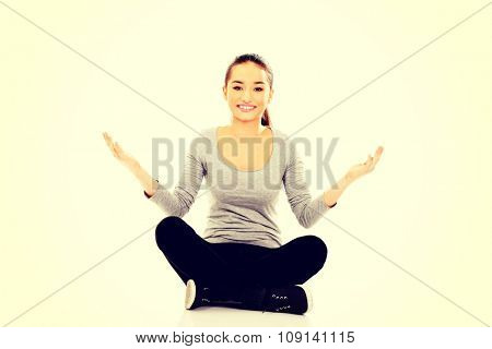 Young woman sitting cross legged with open hands.