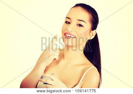 Happy young woman applying cream moisturizer.