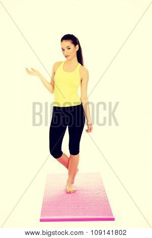 Beautiful athletic woman in sportswear with empty hand.
