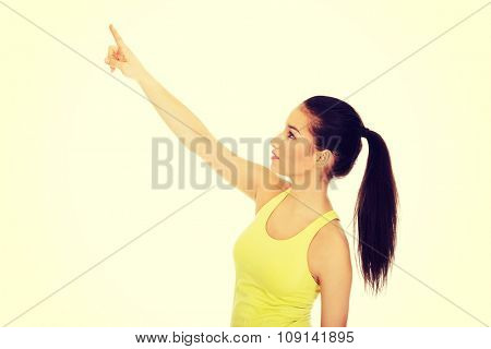 Beautiful athletic woman in sportswear pointing up.