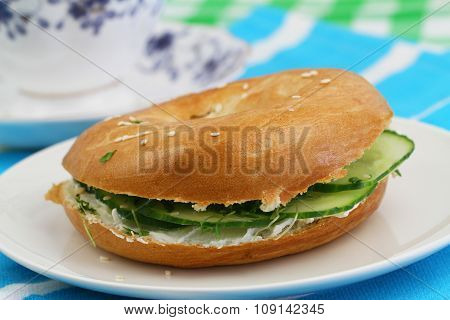 Bagel with cream cheese, cucumber and watercress, closeup