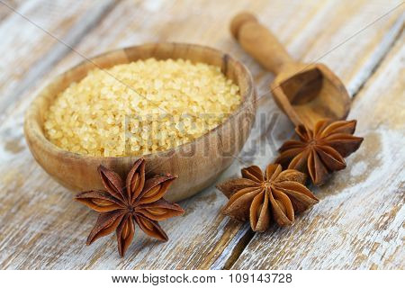 Brown sugar in wooden bowl and star anise on rustic wooden surface