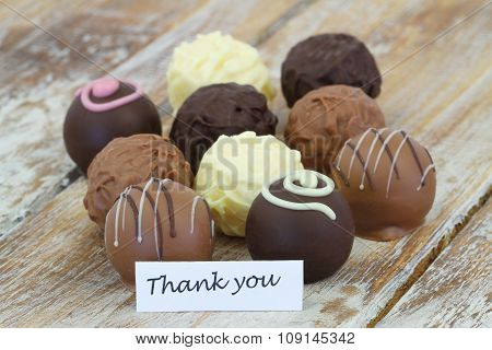 Thank you card with assorted chocolates, truffles and pralines on rustic wooden surface