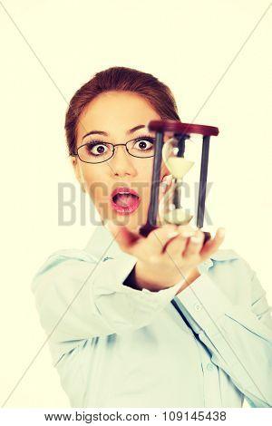 Beautiful shocked businesswoman holding a sandglass.