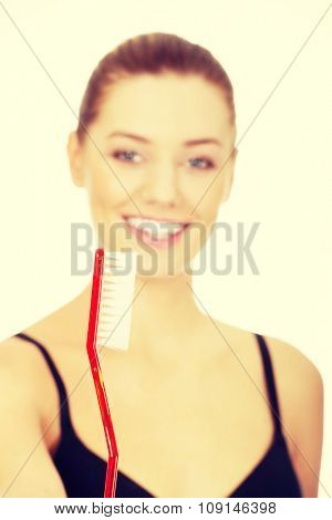 Young woman with oversized toothbrush.