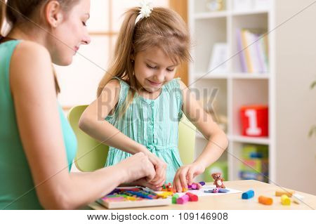 child kid and woman play colorful clay toy at nursery or kindergarten