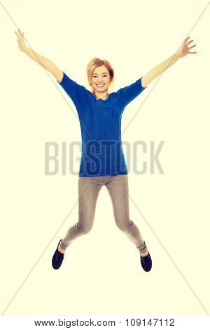Young casual student woman jumping.