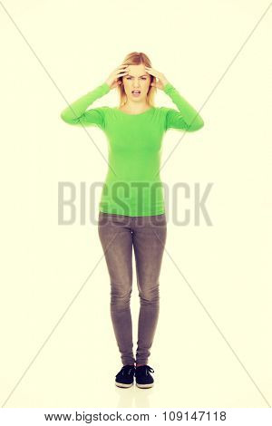 Young angry woman holding her head.