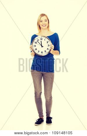 Young happy woman holding a clock.