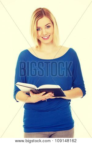 Young caucasian woman reading a book.